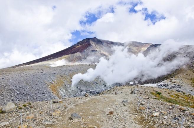 ปากปล่องภูเขาไฟที่มีควันพวยพุ่งตลอดเวลา ด้านหลังที่เห็นคือส่วนหนึ่งของยอดเขา หากจะไปยังจุดสูงสุดสามารถขึ้นได้จากทางเดินริมบึง Sugatami
