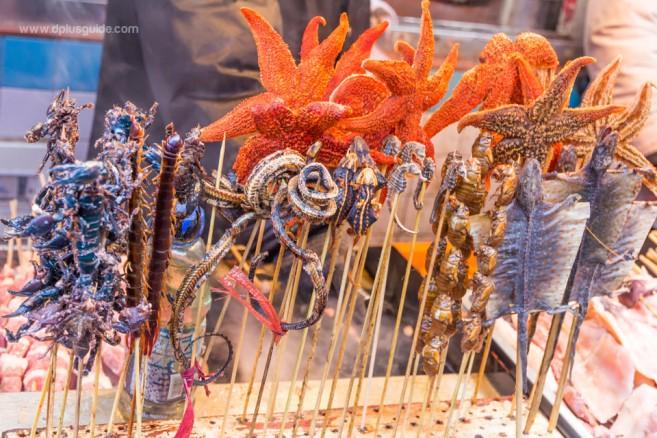อาหารแปลกพิสดารที่มีให้เลือกที่ถนนหวังฟูจิง Wang Fu Jing เช่น แมงป่อง งู ปลาดาว ไข่จั๊กจั่น ม้าน้ำ ปลาดาว ฯลฯ แบบไม้เสียบ