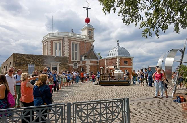 นักท่องเที่ยวต่อแถวกันถ่ายรูปที่เส้น Prime Meridian (Longtitude 0) หน้าหอสังเกตการณ์กรีนิช ชานกรุงลอนดอน  [credit Daniel Case - CC BY-SA 3.0 via Wikimedia Commons]