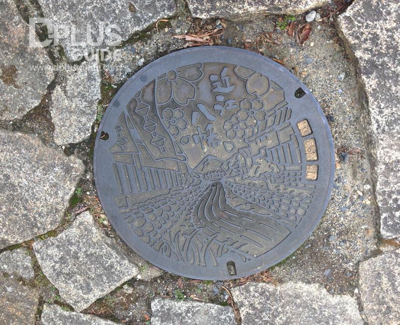 ฝาท่อเมืองโอมิฮาจิมังมีความโด่งดังเรื่องบ้านเรือนเก่า และล่องคลองชมซากุระ